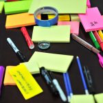 sticky notes and colored pens office supplies on table