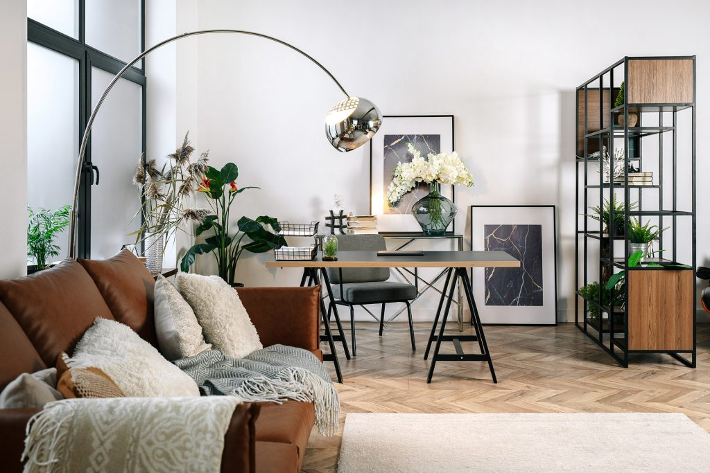 Home office in living room with modern interior design, comfort sofa, laptop computer, paper documents on work desk near armchair. Cozy apartment with decor, picture, bouquet in vase and houseplants